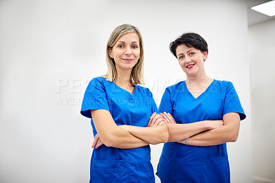 Buy stock photo Portrait of two attractive young nurses posing together with their arms folded at a clinic