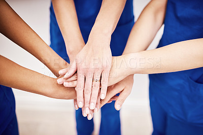 Buy stock photo Shot of an unrecognizable group of nursed joining their hands together in a hurdle against a grey background