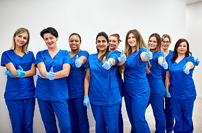 Buy stock photo Portrait of a group pf female nurses posing with their thumbs up at a clinic
