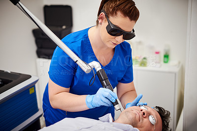 Buy stock photo Shot of a young female nurse wearing eye protection performing laser treatment on a patient at a beauty clinic