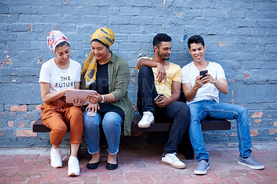 Buy stock photo Full length shot of a young group of muslim friends sitting against a gray brick wall while using wireless devices