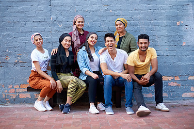 Buy stock photo Portrait of a happy young group of muslim friends posing together against a grey brick outside wall