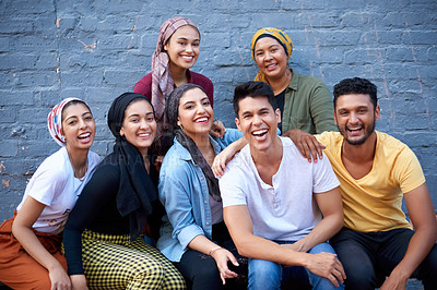 Buy stock photo Cropped shot of a happy young group of muslim friends posing together against a grey brick outside wall