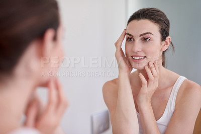 Buy stock photo Shot of a beautiful young woman feeling her skin during her beauty routine at home