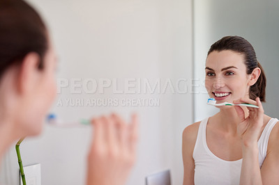 Buy stock photo Shot of an attractive young woman brushing her teeth in the bathroom at home