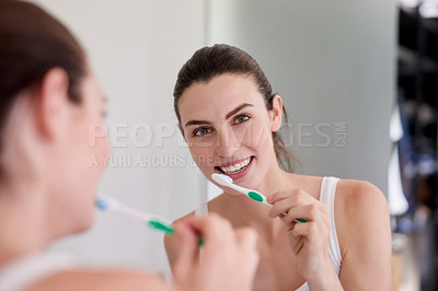 Buy stock photo Portrait of an attractive young woman brushing her teeth in the bathroom at home