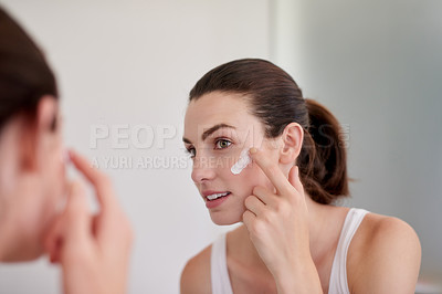 Buy stock photo Shot of an attractive young woman applying moisturiser in front of a bathroom mirror