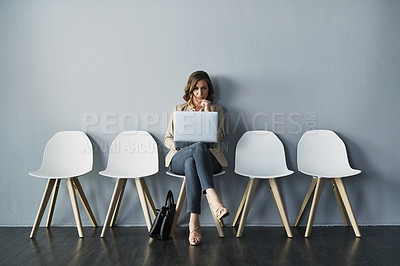 Buy stock photo Full length studio shot of an attractive young businesswoman sitting with her hand on her chin while using her laptop