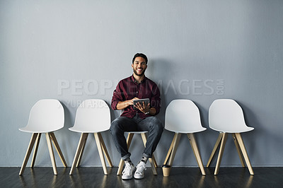 Buy stock photo Portrait of a handsome young man using a tablet while sitting and smiling against a gray studio background