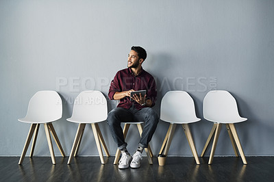 Buy stock photo Full length shot of a handsome young businessman holding a tablet while sitting against a gray studio background