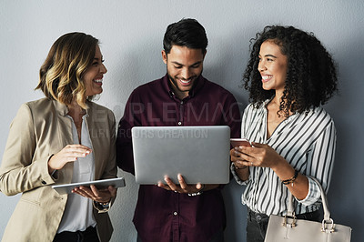Buy stock photo Cropped shot of three young businesspeople talking while using technology against a gray background in the studio
