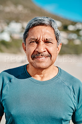 Buy stock photo Cropped portrait of a handsome senior man smiling at the camera while on the beach during the day