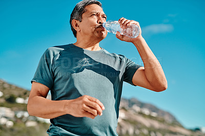Buy stock photo Cropped shot of a handsome senior man drinking water from a bottle on the beach during the day