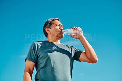 Buy stock photo Cropped shot of a handsome senior man drinking water from a bottle during the day
