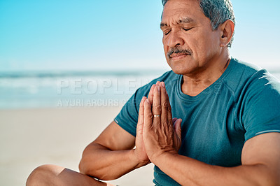 Buy stock photo Cropped shot of a handsome senior man sitting with his legs crossed and meditating on the beach during the day