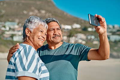 Buy stock photo Cropped shot of an affectionate senior couple holding each other and posing for a selfie during the day