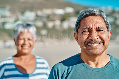 Buy stock photo Cropped portrait of a smiling senior couple standing on the beach together during the day