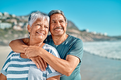 Buy stock photo Cropped shot of an affectionate senior couple standing closely together on the beach during the day