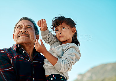 Buy stock photo Cropped shot of an adorable young girl being carried by her grandfather on the beach during the day