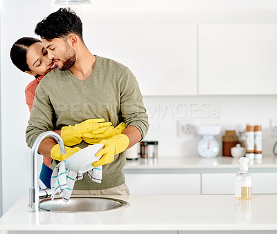 Buy stock photo Shot of a woman embracing her boyfriend while he washes the the dishes