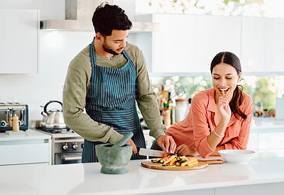 Buy stock photo Shot of a woman keeping her boyfriend company while he chops vegetables
