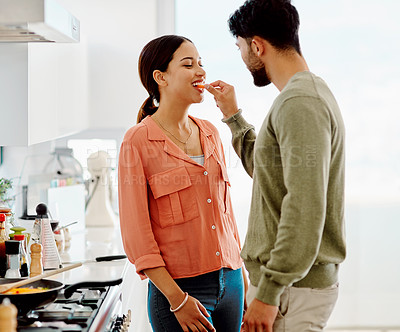 Buy stock photo Shot of a young woman tasting the food that her husband is busy preparing