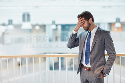 Buy stock photo Shot of a young businessman looking stressed out while standing in an office