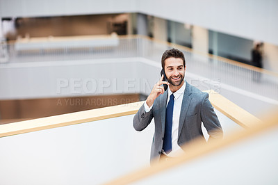 Buy stock photo Shot of a young businessman talking on a cellphone in an office