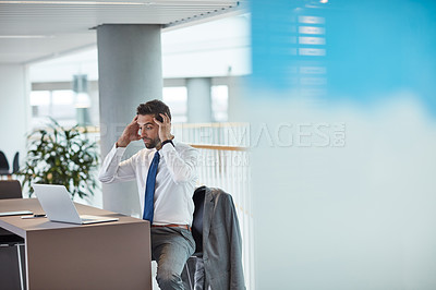 Buy stock photo Shot of a young businessman looking shocked while working on a laptop in an office