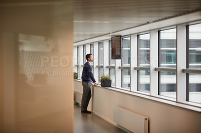 Buy stock photo Shot of a young businessman looking through a window in an office