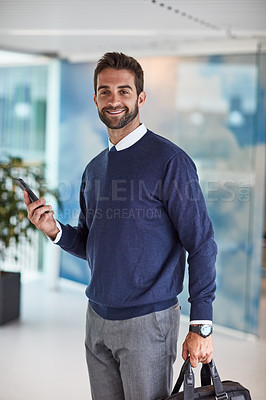 Buy stock photo Portrait of a young businessman holding a cellphone and a bag