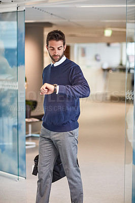 Buy stock photo Shot of a young businessman checking the time on his watch while carrying a bag