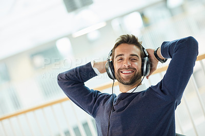Buy stock photo Portrait of a young businessman listening to music in an office