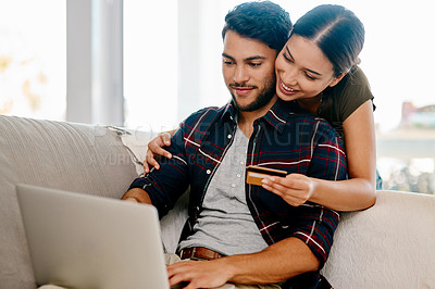 Buy stock photo Shot of an affectionate young couple doing some online shopping together in their living room at home