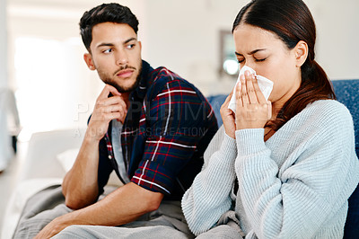 Buy stock photo Shot of a young man getting irritated by his sickly girlfriend blowing her nose next to him at home