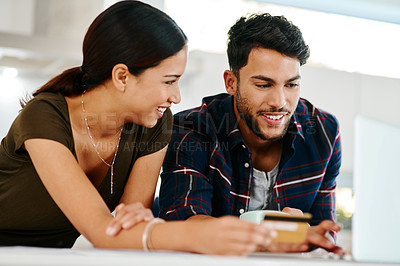 Buy stock photo Shot of an affectionate young couple doing some online shopping together in their kitchen at home