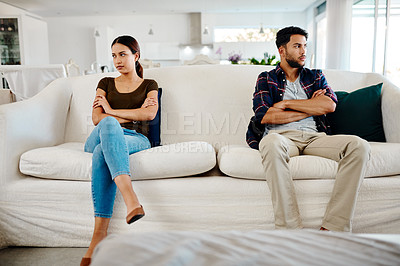 Buy stock photo Shot of a young couple sitting on separate sides of a couch after having an argument at home