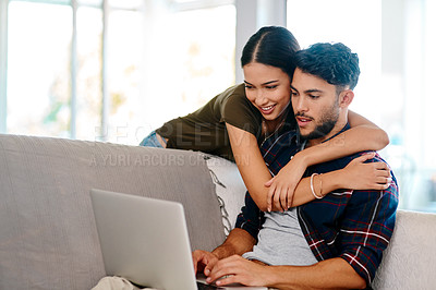 Buy stock photo Shot of an affectionate young couple using a laptop together in their living room at home