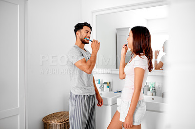 Buy stock photo Shot of a young couple brushing their teeth together in their bathroom at home