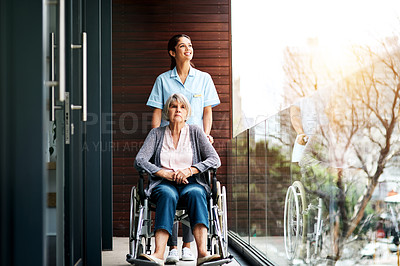 Buy stock photo Shot of a young nurse taking a senior woman out on the balcony with her wheelchair