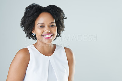 Buy stock photo Cropped studio portrait of an attractive young woman standing and smiling against a gray background