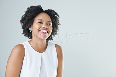 Buy stock photo Cropped shot of an attractive young woman standing and laughing against a gray background in the studio