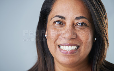Buy stock photo Cropped headshot of an attractive mature woman smiling at the camera while standing against a gray background in the studio