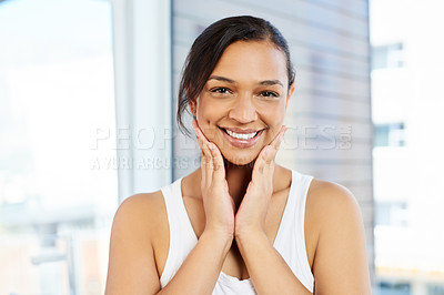 Buy stock photo Cropped portrait of a attractive young woman standing with her hands on her cheeks in her bathroom at home