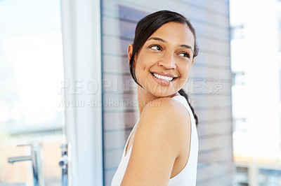 Buy stock photo Cropped shot of an attractive young woman smiling over her shoulder while standing in her bathroom at home