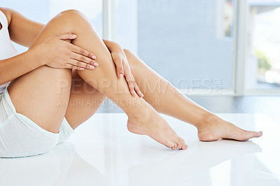 Buy stock photo Cropped shot of an unrecognizable young woman caressing her legs while sitting on the floor at home
