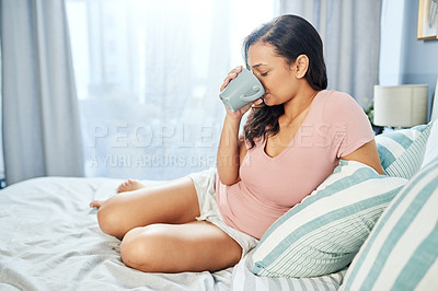 Buy stock photo Shot of a relaxed young woman drinking coffee while being being seated on her bed at home