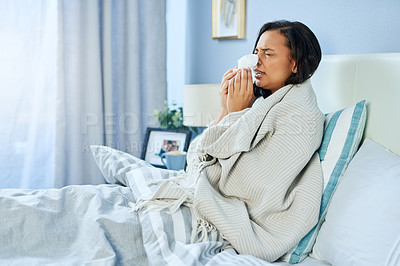 Buy stock photo Shot of an uncomfortable looking young woman blowing her nose while lying in bed at home