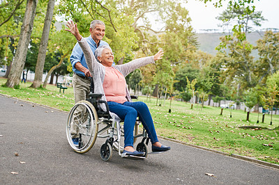 Buy stock photo Full length shot of a smiling senior man pushing his overjoyed senior wife in a wheelchair in the park