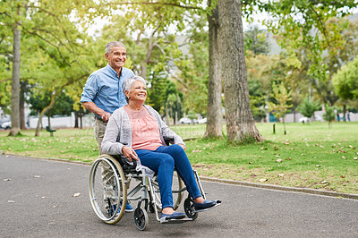 Buy stock photo Full length shot of a smiling senior man pushing his happy senior wife in a wheelchair in the park